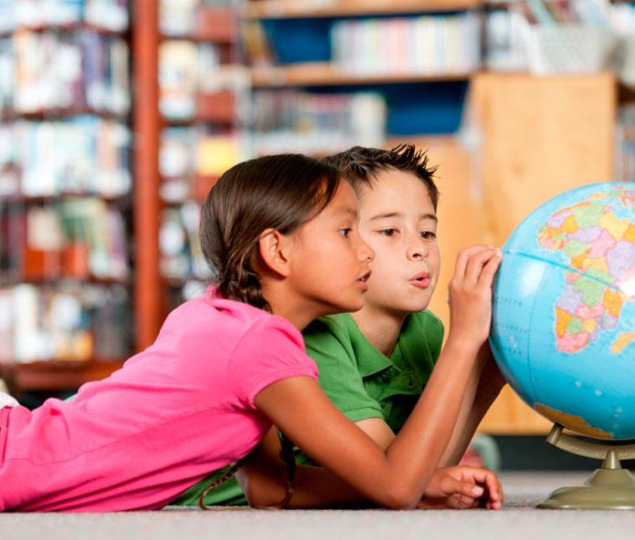 children gazing at globe